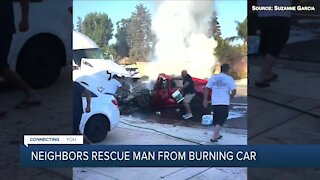 Neighbors rescue man from burning car