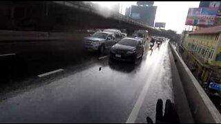Helt på motorsykkel stopper trafikken for å redde en kattunge