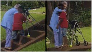 Bimbo aiuta anziana signora a salire le scale