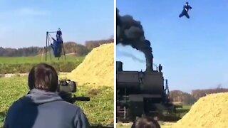 Acrobat performs insane stunt over high speed train