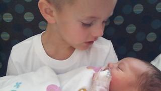Little boy meets newborn baby brother