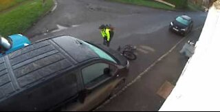 Cyclist slips on rainy road and crashes into a van