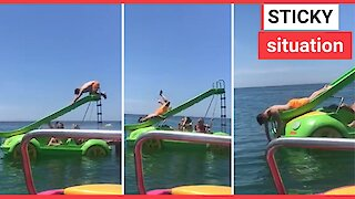 Gallant holiday-goer gets stuck going down slide