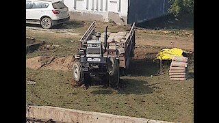 Tractor doing stunts after getting stuck in the mud.