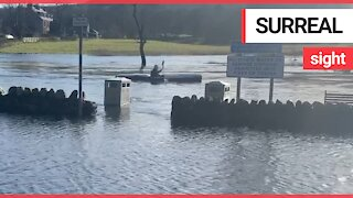 Hilarious moment man is seen kayaking through flooded car park