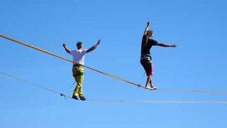 Slackliner performs dangerous trick hundreds of feet above the ground