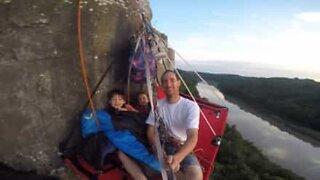 Pai e filhos acampam pendurados numa montanha