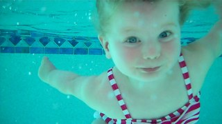 Talented toddler swims and floats in pool