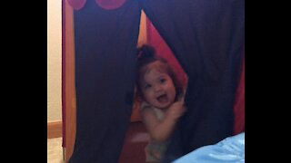 Adorable baby girl plays peek-a-boo with mom