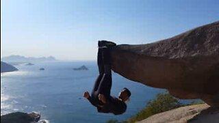 Gutt henger etter føttene på en klippe i Brasil