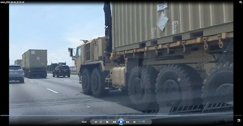 A military convoy of heavy transports hauling shipping containers on I-85 Atlanta