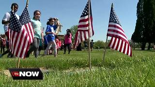 Students place flags in cemetery for Memorial Day