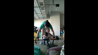 Toddler learning to deadlift with a weight bar