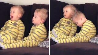 Toddler falls asleep during cartoons, twin brother helps him stay awake