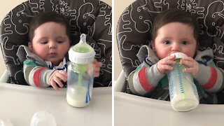 Determined baby attempts to hold bottle on his own