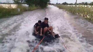 Wakeboarding på en oversvømt vei i Thailand