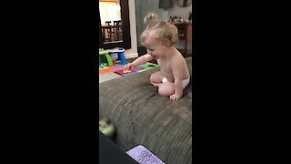 Baby girl can't stop laughing as she plays fetch with dog