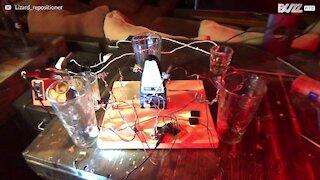 Jovem faz música com um metronomo e copos de água
