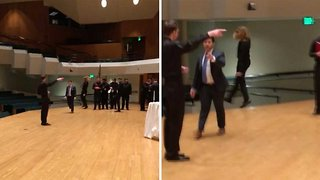 Oblivious student falls off the side of stage while dancing