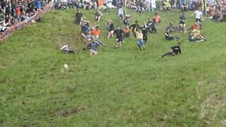 People from around throw themselves down a hill for cheese