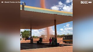 Dust devil forms next to gas station