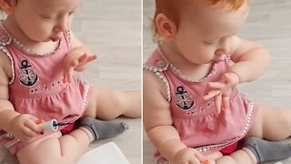 Adorable baby girl applies nail polish, blows on fingers to dry them