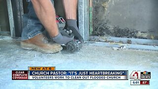 Volunteers work to clean out flooded church
