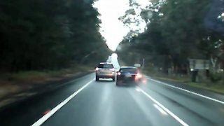 Reckless driver overtakes cars in wet road conditions