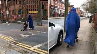 Engelsk mor triller barnevogn med rulleskøyter på seg