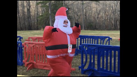 Santa running through a river, and a guy tripping