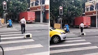 After some fast food? Bizarre moment pedestrian walks microwave across busy zebra crossing