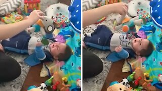 Baby has uncontrollable giggles from playing with his mommy