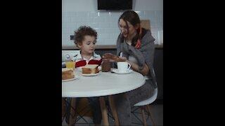 Happy Toddler child- having breakfast with women
