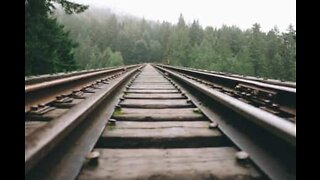 Man lays on train tracks and survives speeding train