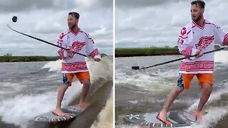 Hockey Fan Makes A Splash By Balancing Puck On Stick As He Surfs