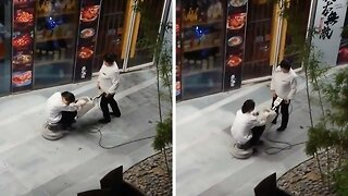 LAZY MALL WORKER SITS ON FLOOR BUFFER AS COLLEAGUE DOES ALL THE WORK