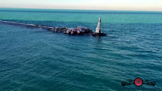 Relaxing drone footage of frozen lakeshore & lighthouse waves