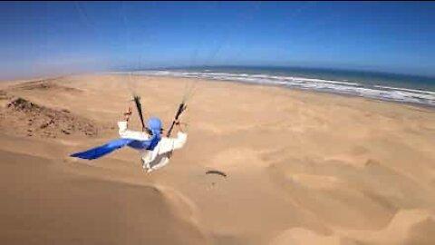 Jovem faz paragliding sobre praia marroquina