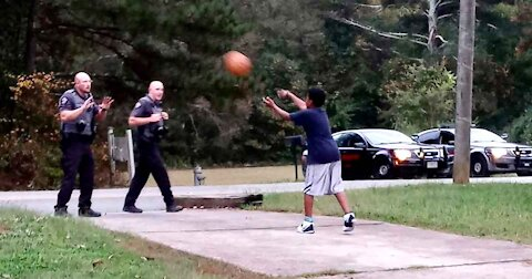 Police Officers Play Basket Ball With Young Boy