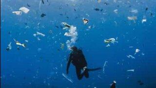 Dykker svømmer i et hav av søppel