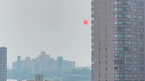Complete red sun rises over New York City