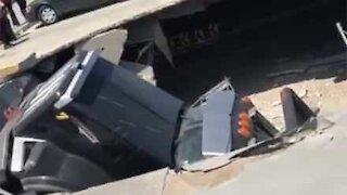 Camião do lixo cai dentro de centro comercial após estacionamento ceder