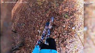 Jovem esquia em folhas de outono