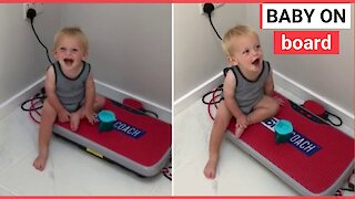 Toddler giggles as he sits on exercise board