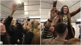 Crowd sings in unison at London underground station