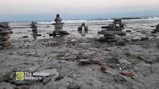 Inukshuks keep watch over rocky shore