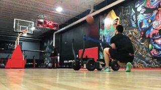 Basketball player slam dunks using slingshot