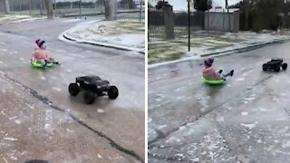 Kid gets pulled by high-powered RC truck on icy road