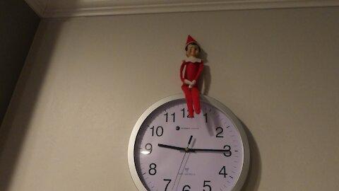 Elf on the Shelf sits on Clock