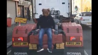 Man with bear mask hitches ride on back of truck